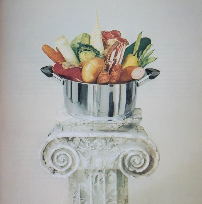 """Die Illustration eines Eintopfs von 1978: die unverarbeiteten Lebensmittel werden in einem Topf auf einer ionischen Säule präsentiert. In dem Kochbuch """"Bon Appétit"""" von Gisela und Ludwig Nau wird auch auf """"ernährungspsychologisch wichtige Fakten hingewiesen"""", wie es im Vorwort heiß."""