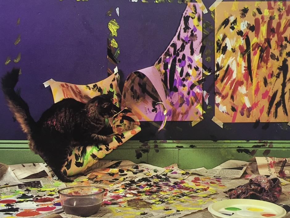 """""""Mit temperamentvollen Schwung verteilt Tiger seine Farben über die drei Papierflächen. Seine raschen, rhythmischen Pfotenhiebe erzeugen eine Struktur von erstaunlicher Komplexität. Anschließend entfernt er die Blätter, so daß große leere Flächen zum Vorschein kommen - ein negativer Raum, in den er dann sein Schlußmotiv malt."""""""